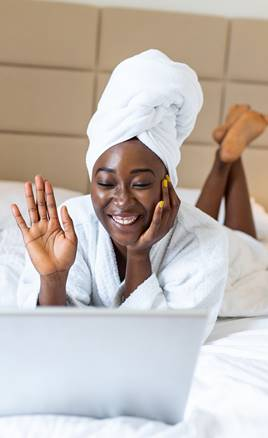 Woman lying on bed after shower, dressed in robe and using laptop