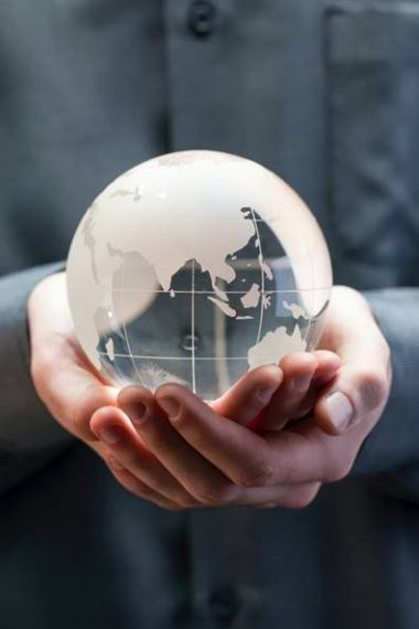 Person holding a world globe in the palm of their hands